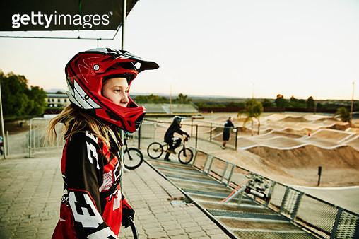 Portrait of female BMX racer looking at track before race start - gettyimageskorea
