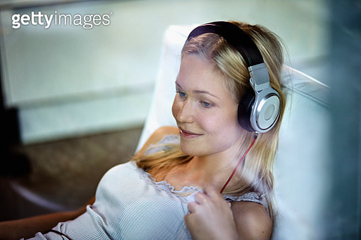 Smiling young woman wearing headphones listening to music on lounge chair at home - gettyimageskorea