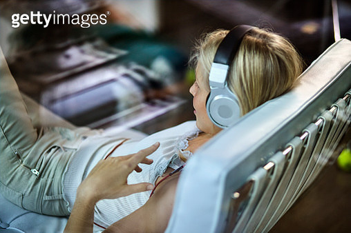 Young woman wearing headphones listening to music on lounge chair at home - gettyimageskorea