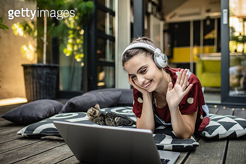 Young woman at home with headphones is on a video call with her friends - gettyimageskorea