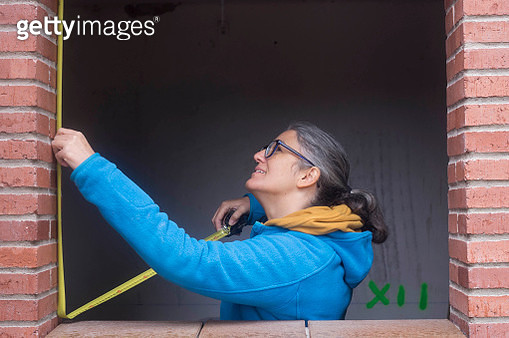 Female architect measuring window at construction site - gettyimageskorea