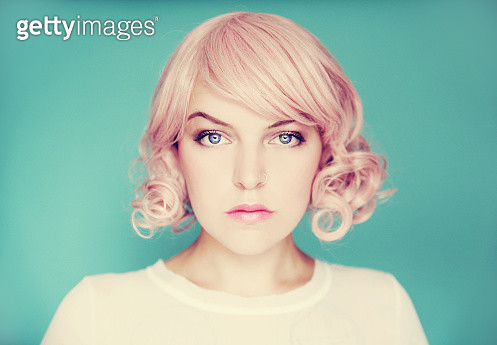 Young beautiful woman with pink curly hair on a blue backdrop - gettyimageskorea