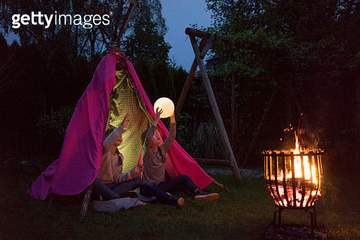 Two girls standing in front of tipi, holding lamp as moon - gettyimageskorea