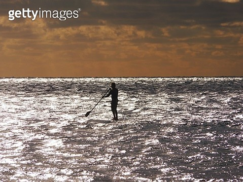 Silhouette Man Paddleboarding In Sea Against Sky During Sunset - gettyimageskorea