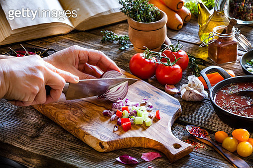 Cutting fresh vegetables on rustic wooden kitchen table - gettyimageskorea