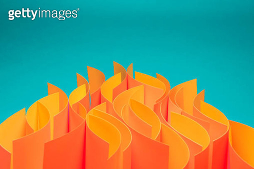 Orange and yellow sheets of paper on edge on blue / green background in wave pattern to mimic fire - gettyimageskorea