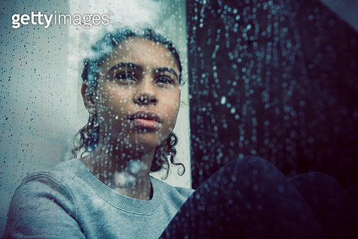 Girl staring out of rainy window - gettyimageskorea