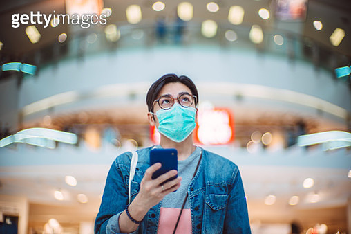 Young handsome Asian man in medical face mask using smartphone joyfully in shopping mall - gettyimageskorea