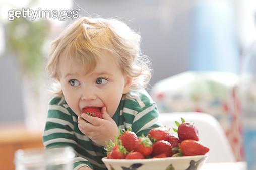 Toddler eating strawberries - gettyimageskorea