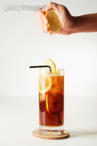 Hand Squeezing Lemon into Iced Tea - gettyimageskorea