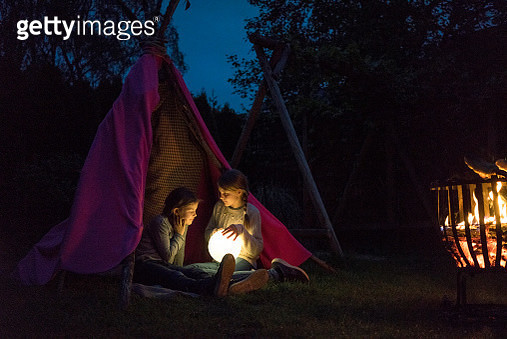 Two girls sitting in tipi, holding lamp as moon - gettyimageskorea