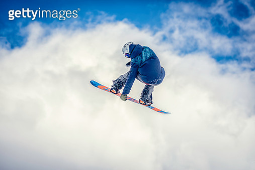Snowboarder in mid-air doing a melon grab - gettyimageskorea