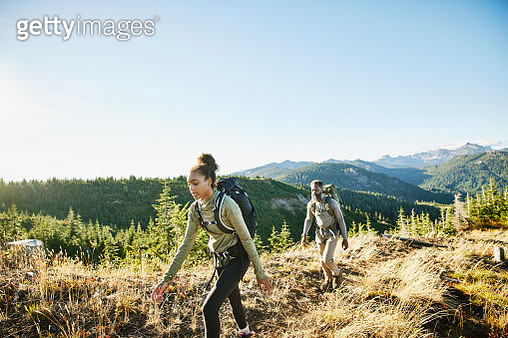 Daughter and father hiking on ridge during backpacking trip - gettyimageskorea