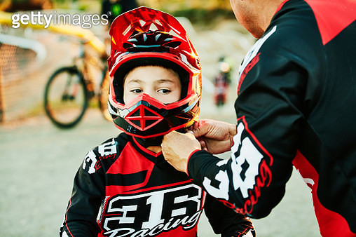 Father helping son buckle up helmet before BMX race - gettyimageskorea