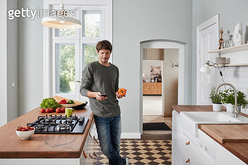 Man using smartphone and holding bell pepper in kitchen - gettyimageskorea