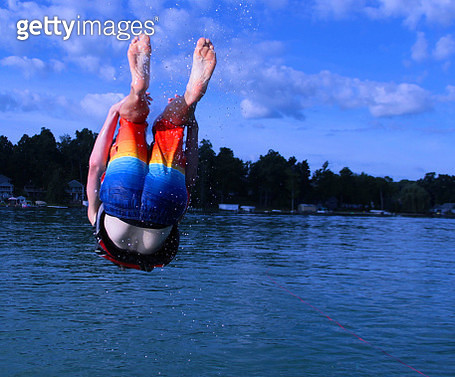 Man Wearing Multi Colored Swimming Trunks Diving In Sea Against Sky - gettyimageskorea
