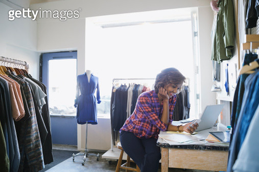 Business owner working at laptop in clothing shop - gettyimageskorea