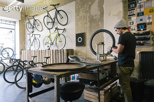 Mechanic working on tire in a custom-made bicycle store - gettyimageskorea