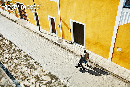 Overhead view of gay couple carrying luggage while walking down street in small town on vacation - gettyimageskorea
