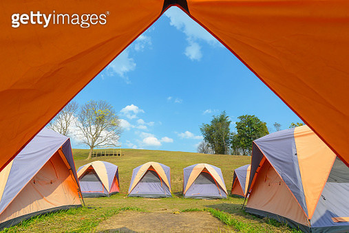 Tents On Grassy Field Against Blue Sky - gettyimageskorea