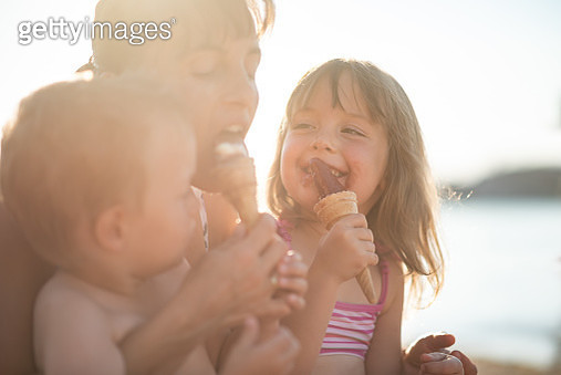 Kids with their mom eating ice cream outdoors - gettyimageskorea