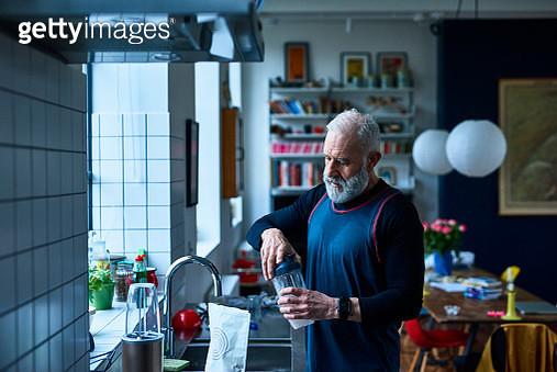 Senior man making protein shake before exercising - gettyimageskorea