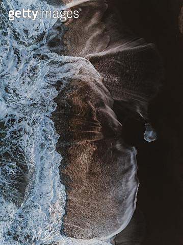 Drone image looking down on crashing ocean waves on Reynisfjara black sand beach, Iceland - gettyimageskorea