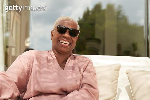 A mature woman laughs joyfully, she sits outside. - gettyimageskorea