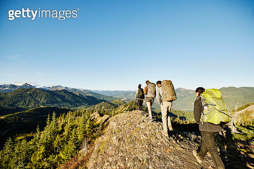 Father and daughters hiking on rocky ridge during backpacking trip - gettyimageskorea