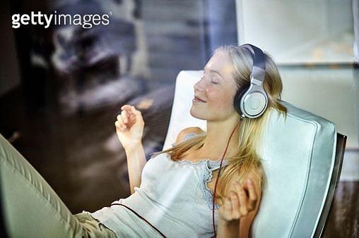 Relaxed young woman wearing headphones listening to music on lounge chair at home - gettyimageskorea
