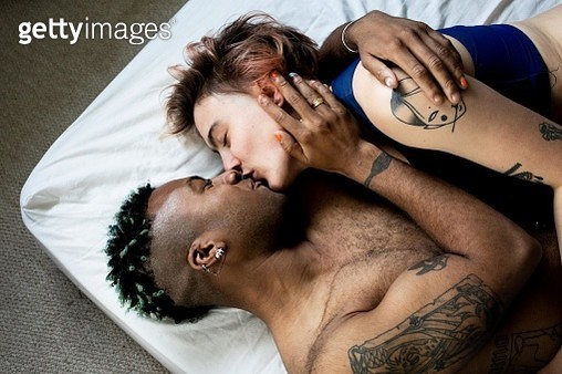 A young LGBT couple kissing and hugging in bed - gettyimageskorea