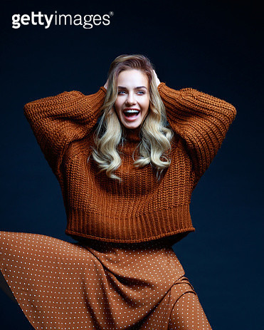 Fashion portrait of long hair blond young woman wearing brown sweater and skirt, laughing with raised hands. Studio shot against black background. - gettyimageskorea