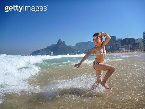 A gril runs from a wave in Ipanema beach, Rio de Janeiro, Beach. - gettyimageskorea