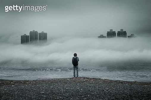 Man standing alone looking out to sea against moody sky during foggy weather - gettyimageskorea
