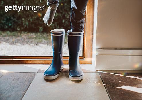 Child putting on Blue Wellington Boots - gettyimageskorea