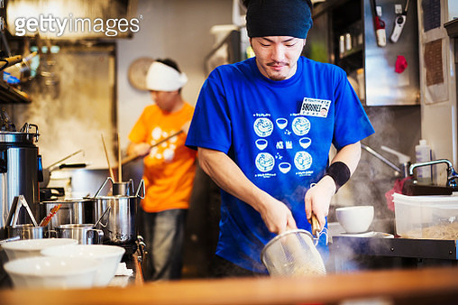 A ramen noodle shop kitchen. A chef preparing bowls of ramen noodles in broth, a speciality and fast food dish.  - gettyimageskorea