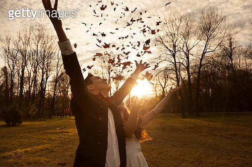 Happy bridal couple in park cheering and throwing leaves - gettyimageskorea