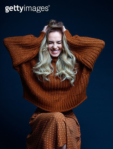 Fashion portrait of long hair blond young woman wearing brown sweater and skirt, smiling with eyes closed and raised hands. Studio shot against black background. - gettyimageskorea