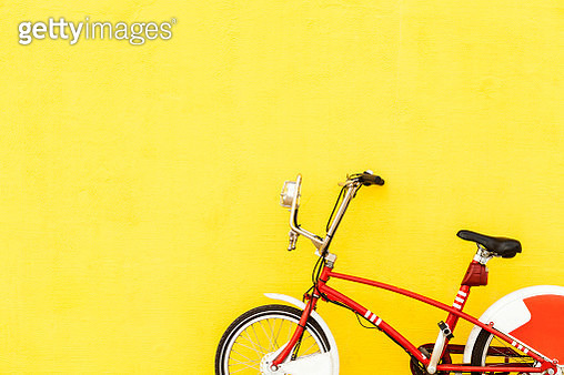 Red bicycle parked at yellow wall - gettyimageskorea