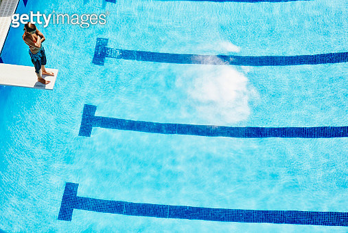 Young boy standing at end of diving board at outdoor pool overhead view - gettyimageskorea