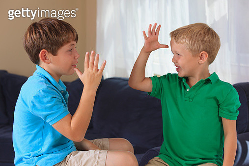 Boys with hearing impairments signing mom, dad or parents in American sign language on their couch - gettyimageskorea
