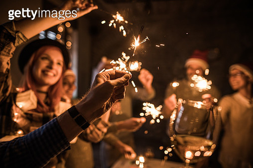Close up of man's hand holding sparkler during a party with his friends. - gettyimageskorea
