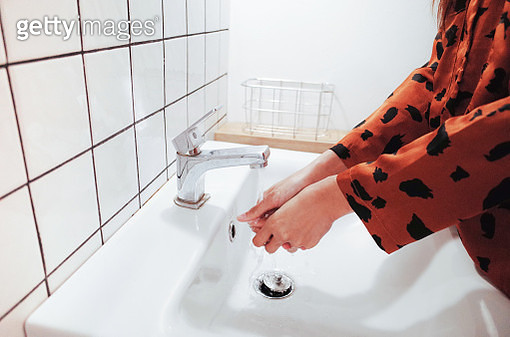 Midsection Of Woman Washing Hands At Sink In Bathroom - gettyimageskorea