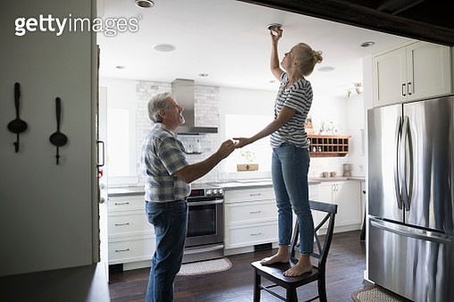 Senior father helping daughter changing light bulb in kitchen - gettyimageskorea