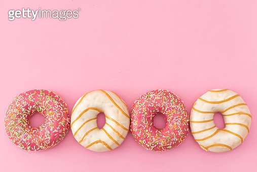 Sprinkled Pink Donut. Frosted sprinkled donut on pink background. - gettyimageskorea