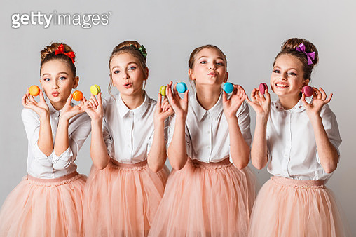 Portrait Of Girls Holding Colorful Macaroons Against White Background - gettyimageskorea