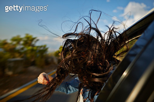 Womans hair blowing with head out of car window - gettyimageskorea