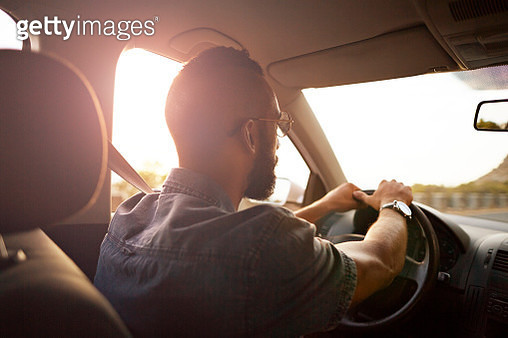 Man driving car in the sunset - gettyimageskorea