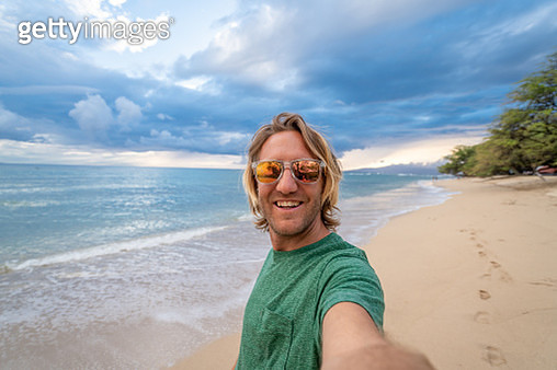 Young man takes selfie portrait on beach at sunset, Hawaii . People travel luxury vacations fun and cool attitude concept - gettyimageskorea