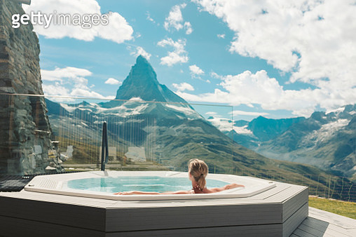 Woman in hot tub looking at mountains - gettyimageskorea